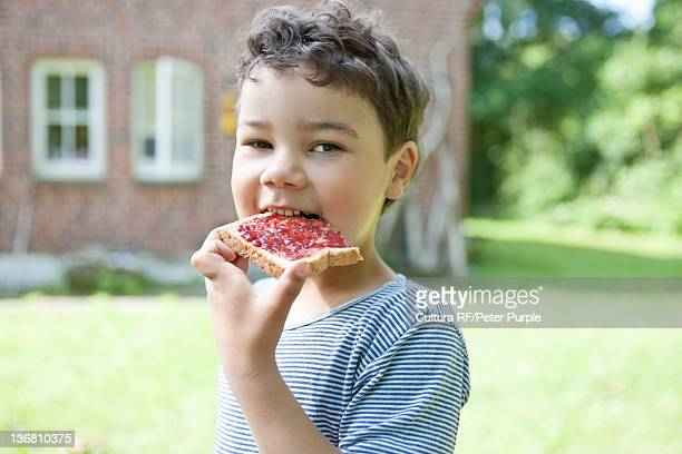 Boy eating bread with jam outdoors