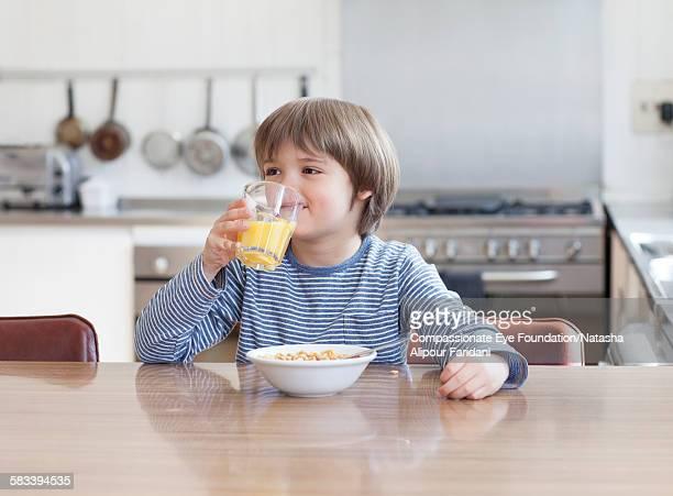 Boy eating breakfast in kitchen