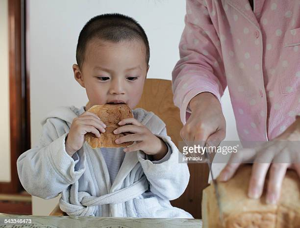 Boy (2-3) eating breakfast