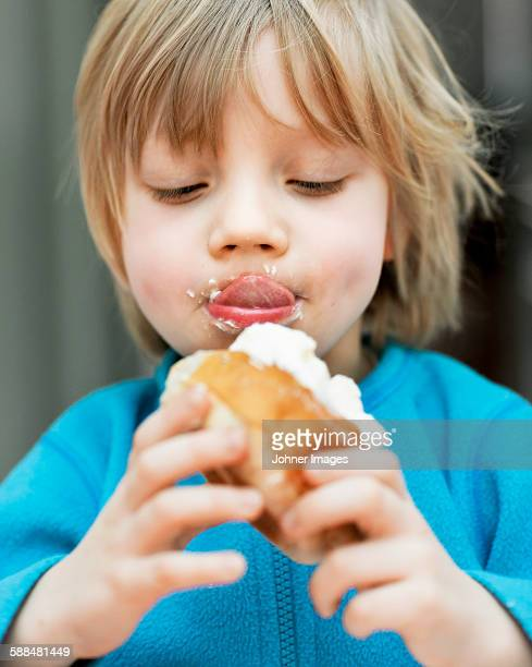 Boy eating bun