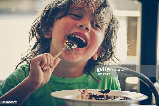Boy eating cake at a cafe.