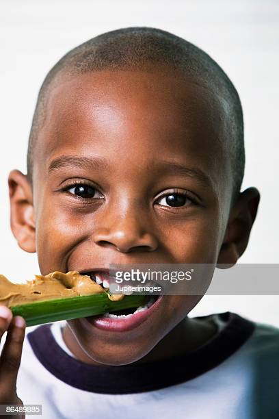 Boy eating celery with peanut butter