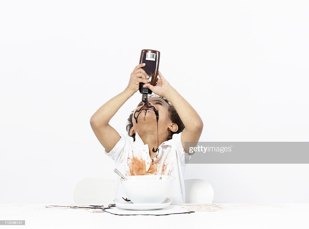 Boy eating chocolate sauce