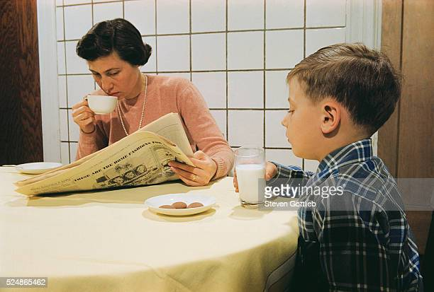 Boy Eating Cookies and Milk as Mom Reads