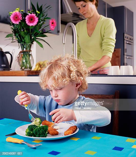 Boy (2-4) eating fish fingers and broccoli, mother at kitchen sink