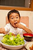 Boy eating fried chicken, Japan