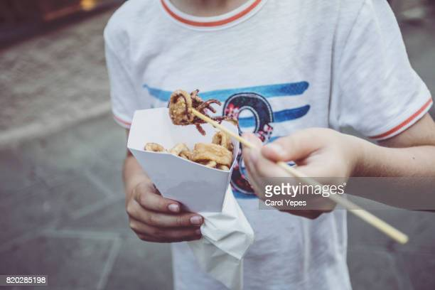 boy eating friends squids in the street