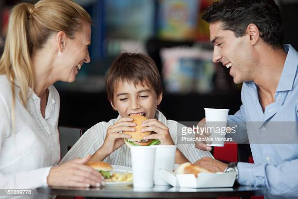 Boy eating hamburger in fast food restaurant with his parents