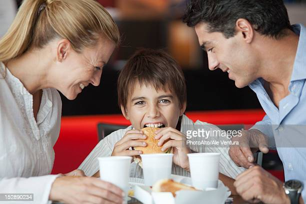 Boy eating hamburger with his parents in fast food restaurant