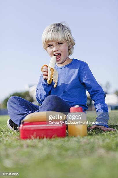 Boy eating his lunch in grass