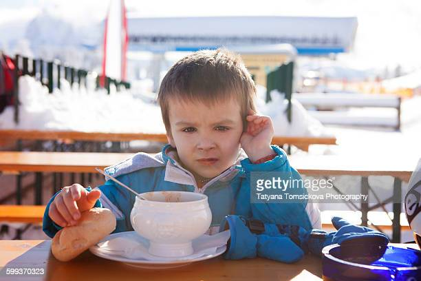 Boy, eating hot soup on top of mountain