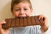Boy eating large chocolate bar