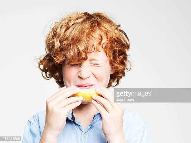 Boy eating lemon