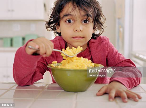 Boy eating macaroni and cheese
