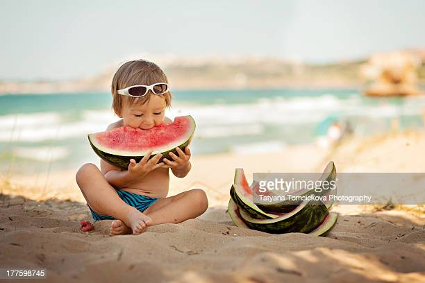 Boy eating piece of watermelon