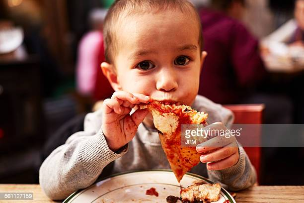 Boy eating pizza in restaurant