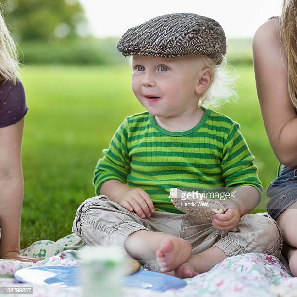 Boy eating rice cake at picnic