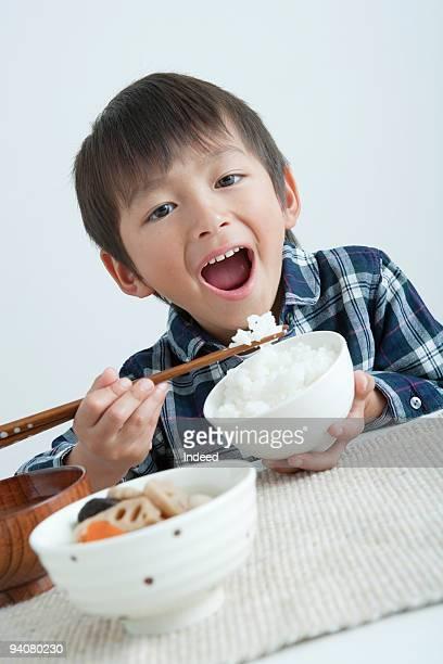 Boy eating rice with chopsticks