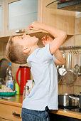 Boy eating spaghetti in kitchen