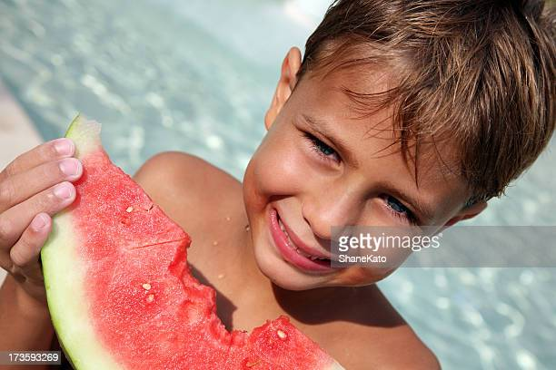Boy eating Watermelon at Swimming Pool on Summer Vacation