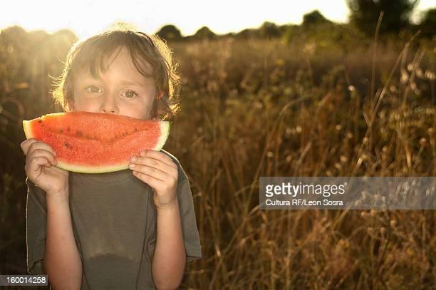 Boy eating watermelon in tall grass