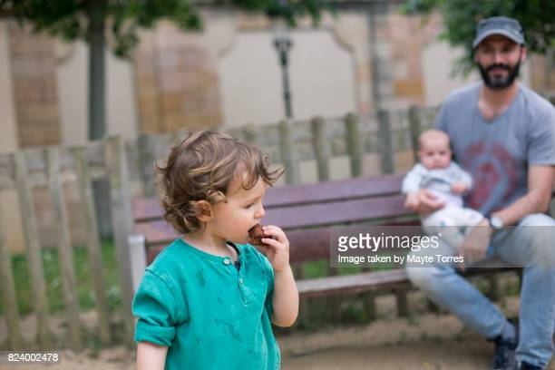 boy eating while dad watches him