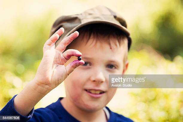Boy eats berries in the forest