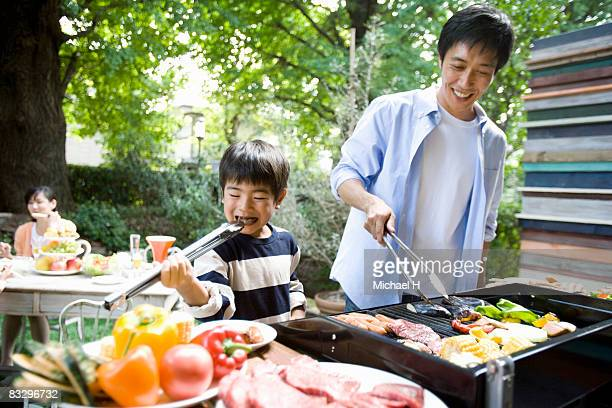 Boy eats by stealth,man cooking barbecue