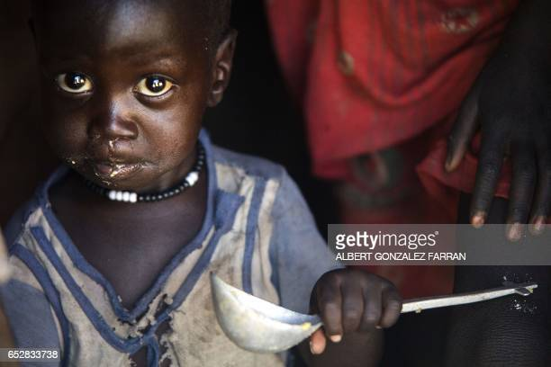 TOPSHOT A boy eats out of a ladle at his home in Ngop in South Sudan's Unity State on March 10 2017 The Norwegian Refugee Council distributed food...