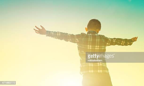 Boy embrace the sun as it sets on the sky