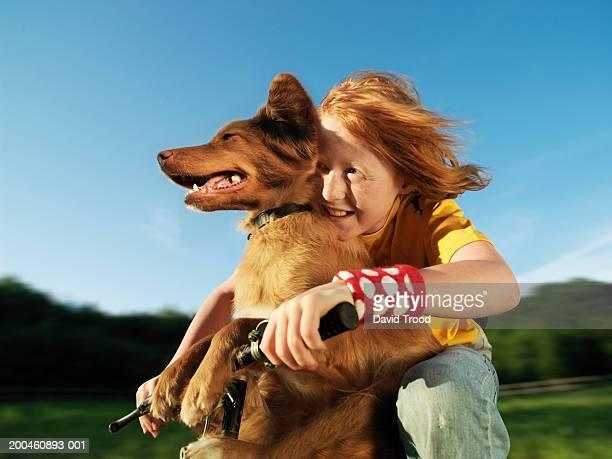 Boy (10-12) embracing dog outdoors, smiling