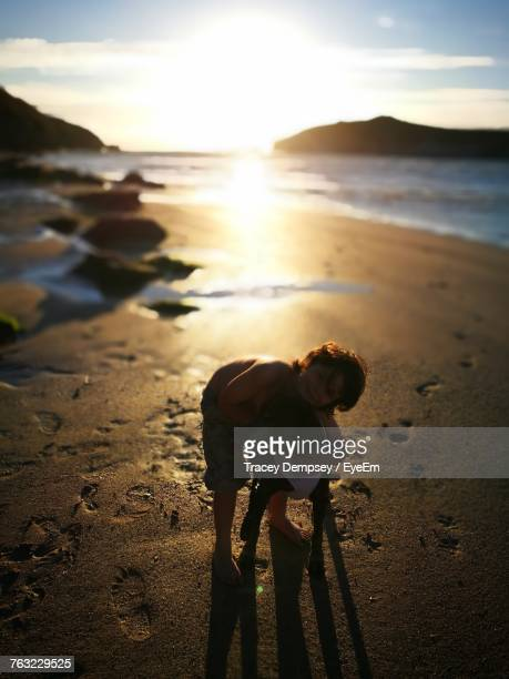 Boy Embracing Dog While Standing On Shore At Beach