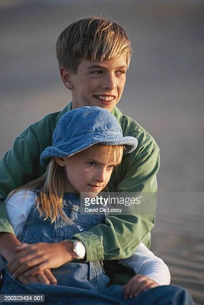 Boy (10-13) embracing girl (6-9) outdoors, looking away