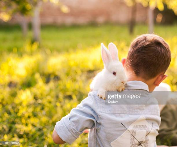 Boy embracing his rabbit in the park