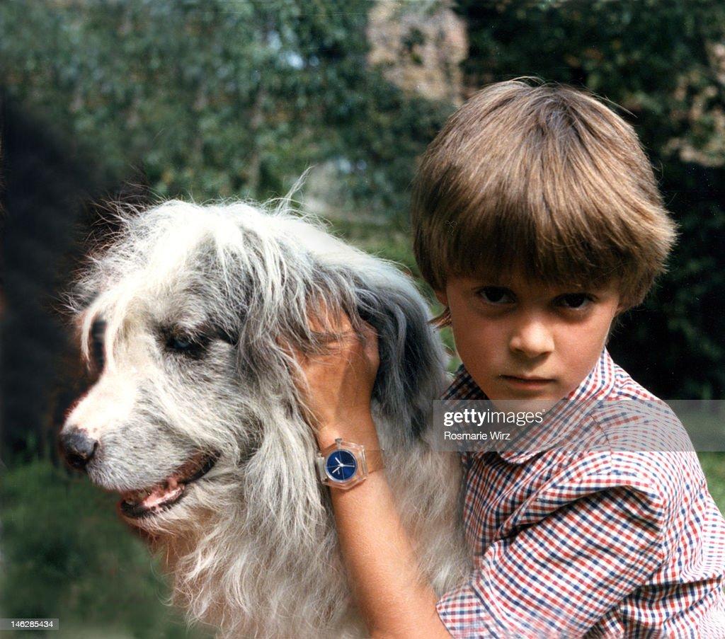 Boy embracing sheepdog : Stock Photo
