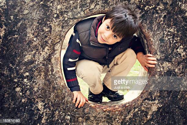 Boy emerging from hole