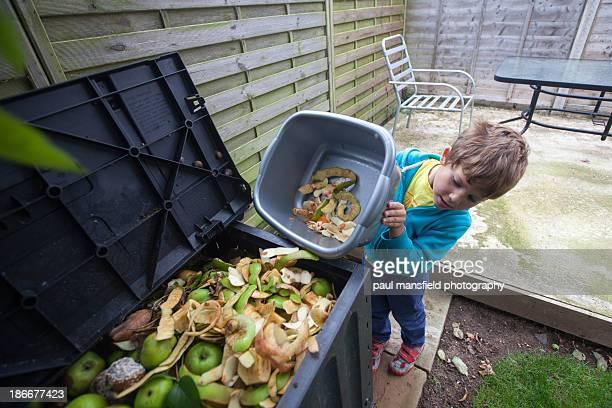 Boy emptying apple peel into compost bin
