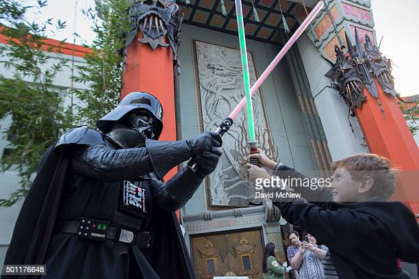 A boy engages David Baxter who is dressed as Darth Vader in a light saber battle as fans camp out in the TLC Chinese Theatre courtyard for the...