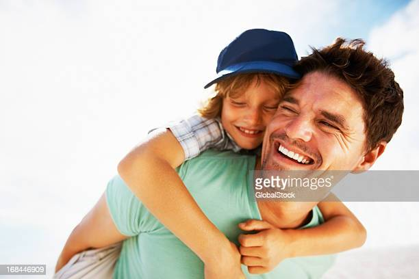 Boy enjoys a piggy back ride on father