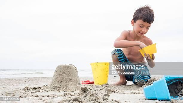 Boy enjoys building a castle in the sand