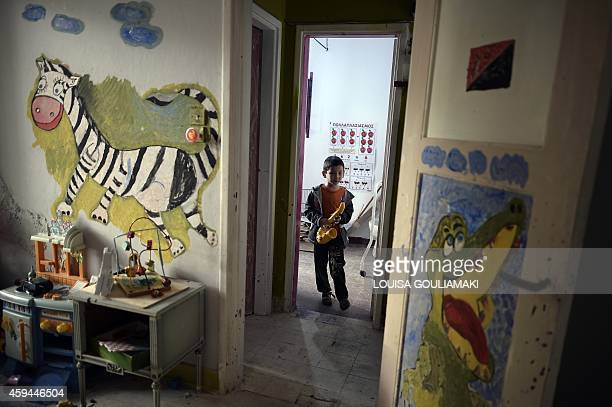 A boy enters a room which acts as a playarea and classroom on the ground floor at the prosfygika complex in central Athens on Novemeber 2 2014 Wedged...