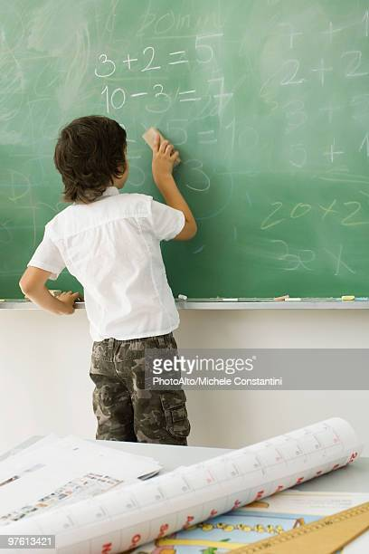 Boy erasing blackboard, rear view