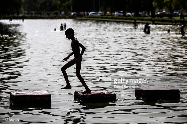 A boy escaping the heat jumps over stones as he and others play in a pond at India Gate monument on May 31 2012 in New Delhi India A Heat wave is...