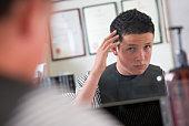 Boy examining haircut