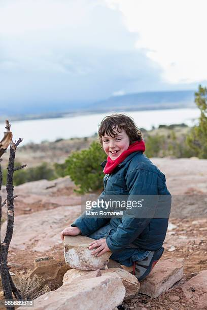 Boy examining rocks on dirt path