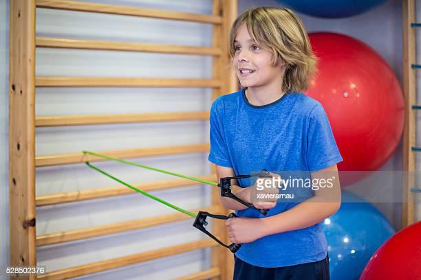 Boy exercising with elastic band at hospital rehabilitation