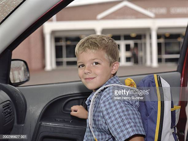 Boy (6-8) exiting car outside school, smiling, portrait