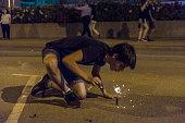 Boy exploding firecrackers at night to celebrate the festivity of Sant Joan on a street in Estartit, Costa Brava, Catalonia, Spain. St John's eve celebration around a bonfire is reminiscent of Midsumm