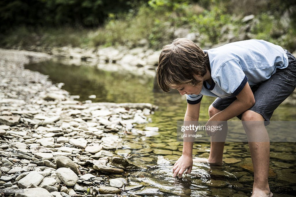 Boy exploring in stream