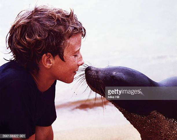 Boy (9-11) face to face with Galapagos sea lion, eyes closed